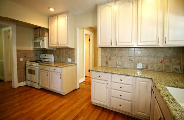 Alternate view of remodeled kitchen with built-in microwave, gas stove, and entry to butler's pantry in the center.