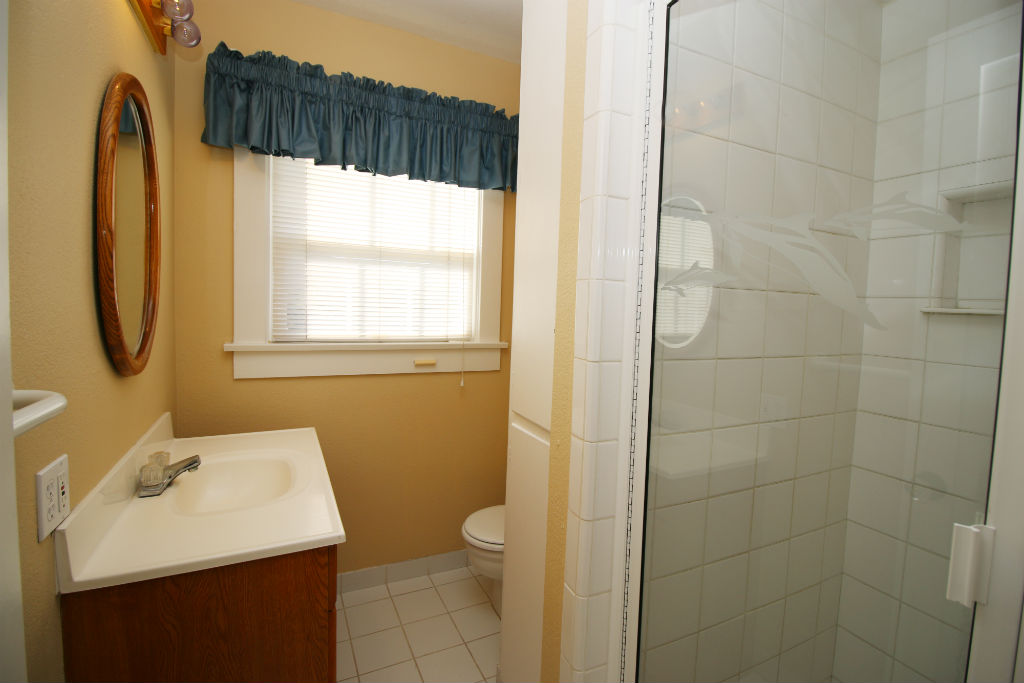 Remodeled three quarter bathroom with tile flooring and shower.