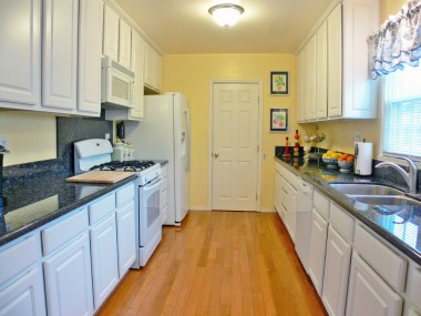 Remodeled kitchen with wood flooring, granite counters, gas stove, dishwasher, built-in microwave, and a huge walk-in pantry.