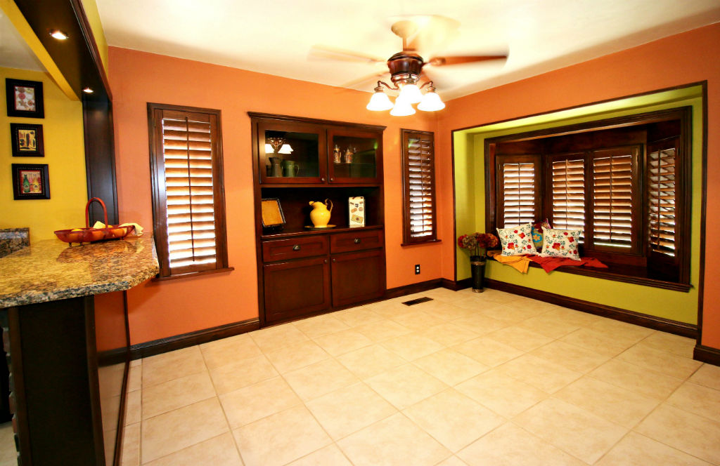 Formal dining room with tile floor, original built-in hutch, window shutters, breakfast bar, and window seat.