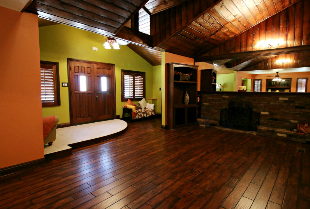mazing interior of home with lots of wood and a step-down living room with fireplace and wood ceiling.