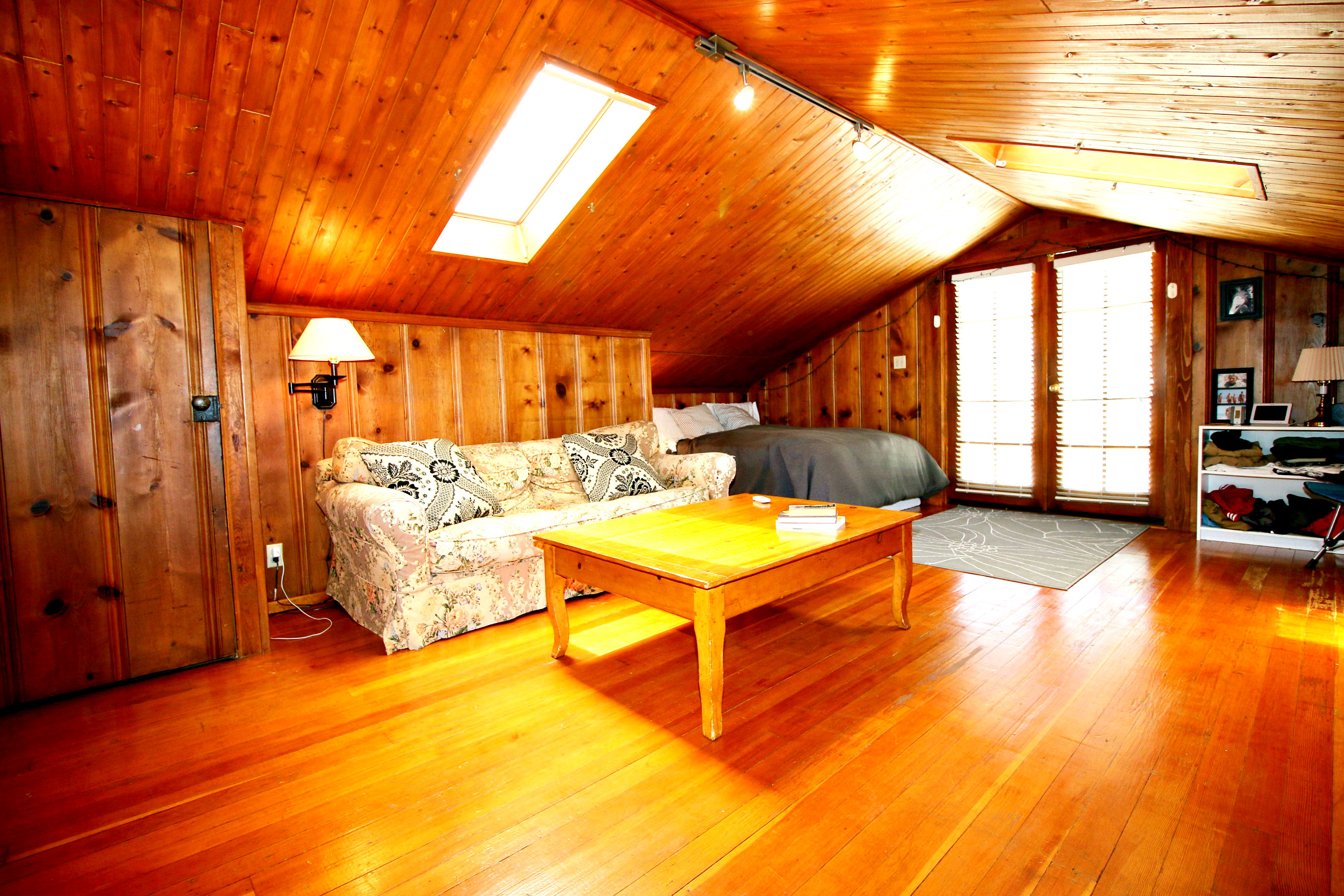 Alternate view of upstairs guest living room/bedroom with skylights and French doors leading to the private sun deck.