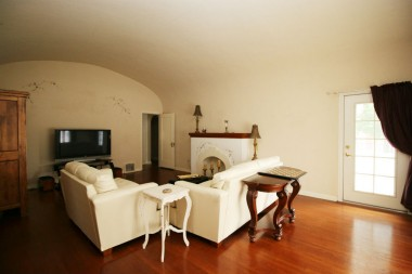 Large living room with dramatic barrel ceiling, decorative fireplace (gas line has been capped off).