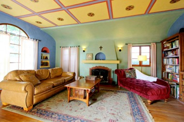 Large living room with dramatic trey ceiling (painted with colors from California missions), built-in display niches flanking large picture window, and original hardwood floors and wood-burning fireplace with alcove!