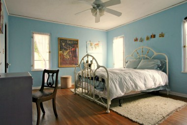 Large back bedroom with original hardwood floors and ceiling fan.