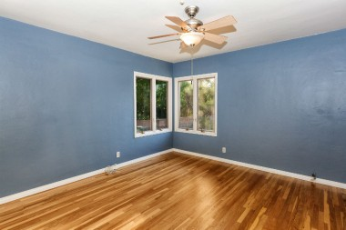 Back bedroom with recently refinished hardwood floors, ceiling fan, and fresh paint.