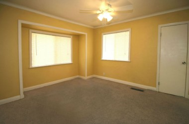 Back bedroom with carpeting, ceiling fan, and two closets.