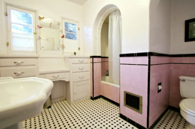 Spacious hallway bathroom with built-in vanity, shower in tub, and pedestal sink. How charming is this!