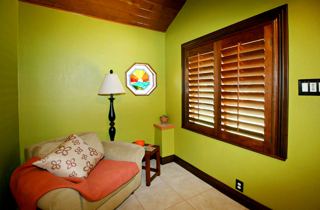 Sitting area of formal entry - tile floor and window shutters, and wood ceiling.