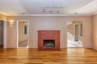 Wood -burning and gas fireplace with track lighting, flanked by entrances into step-down family room.