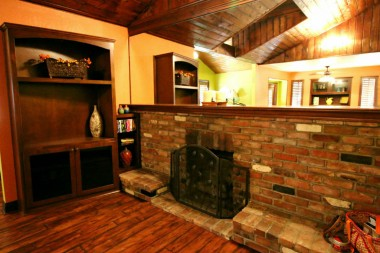 Brick fireplace and built-in TV stand and mantle mirror.