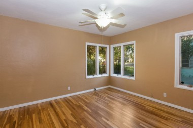 Front bedroom with fresh paint, recently refinished hardwood floors, and ceiling fan.