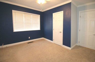 Front bedroom with carpeting and ceiling fan.
