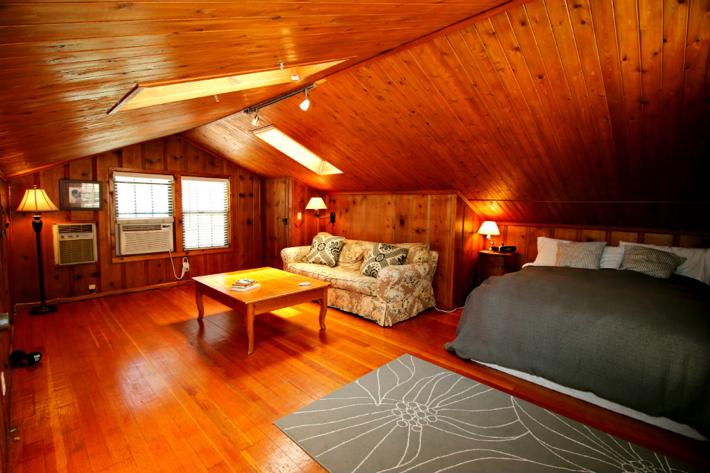 Upstairs living space/bedroom in guest unit. Window a/c unit and wall heater, as well as sky lights, track lighting, and lots of storage.