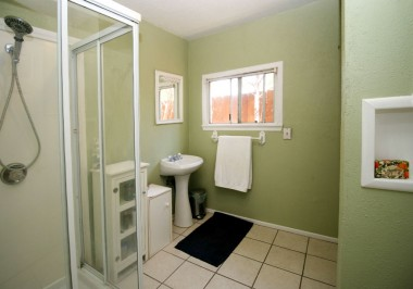 Guest unit 3/4 bathroom with tile flooring and pedestal sink.