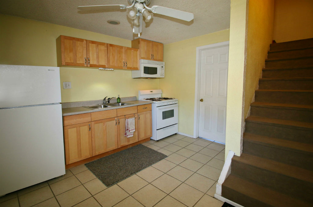 Guest unit kitchenette with doorway to downstairs 3/4 bathroom, and stairway to living room/bedroom.