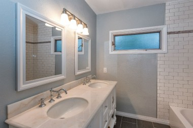 Remodeled hallway bathroom with dual sinks, subway tile in tub/shower, and hands-free toilet.