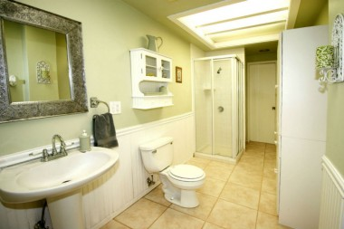 Hallway bathroom with tile floor, pedestal sink, bead board, and built-in linen shelving.