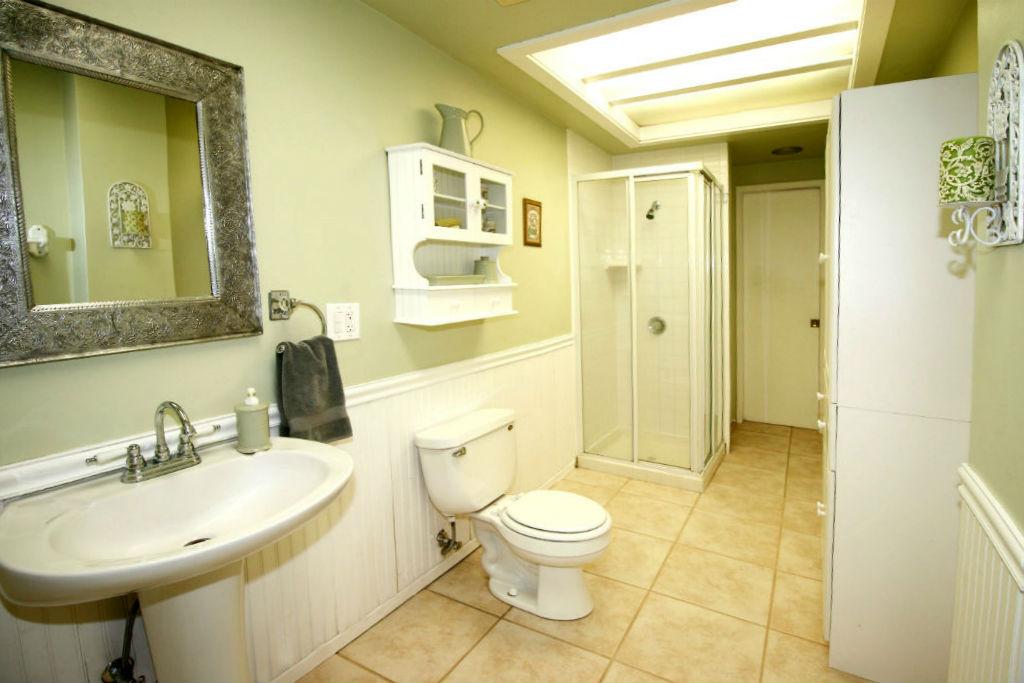 Hallway bathroom with tile floor, pedestal sink, bead board, and built-in linen shelving.