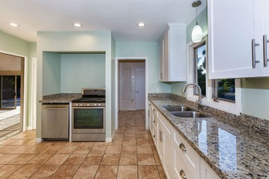 Remodeled kitchen with granite counters, tile floor, self-closing cabinetry, pull-out drawers, brand new gas stove, and brand new dishwasher.