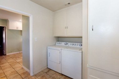 Separate laundry room (washer and dryer are included), lots of cabinetry, and original built-in ironing board.