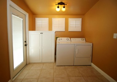 Separate indoor laundry room with cabinetry and tile flooring. Washer and dryer are included.