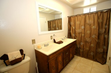 Remodeled master bathroom with tile floor and shower in tub.