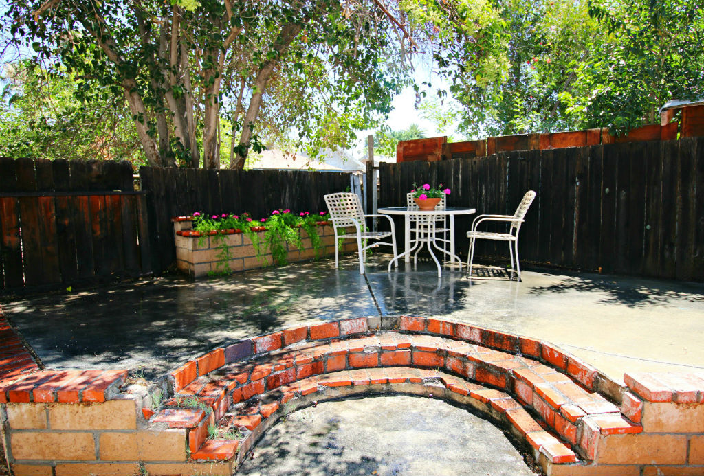 Raised patio in back corner of yard shaded by neighbor's tree, along with a planter.