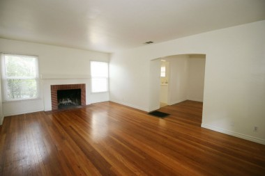 Living room with gorgeous refinished hardwood floors and fireplace.