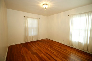 Front bedroom with ample closet space and beautifully refinished hardwood floors.
