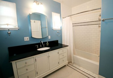 Remodeled bathroom with honeycomb tile floor and subway tile in shower/tub.