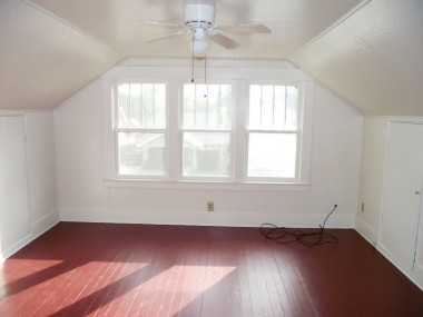 Third of three upstairs bedrooms with ceiling fan and original hardwood floors. How charming is this!