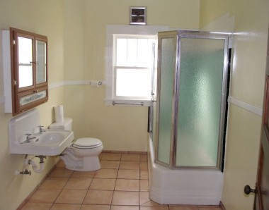 Main floor bathroom with tile floor, original sink, and shower in tub. Upstairs bathroom has only a toilet.