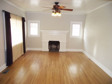 Living room with hardwood floors, fireplace, and ceiling fan.