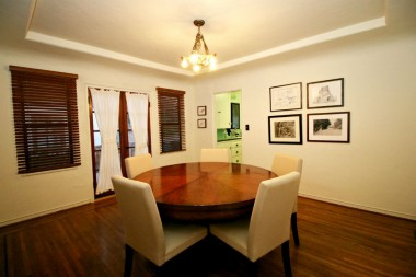 Formal dining room with original hardwood floors and tray ceiling, and period French doors leading to side patio and extra wide driveway.