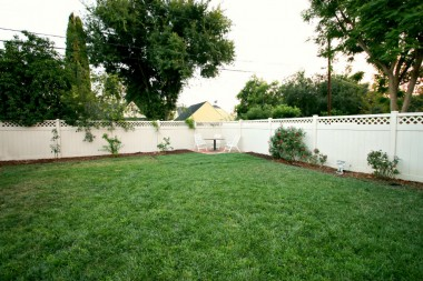 Park-like pool-size backyard with corner patio area and vinyl fencing.