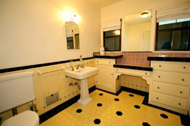 Spacious bathroom with original pedestal sink and wall tile. Flooring was recently laid to match existing original tile.