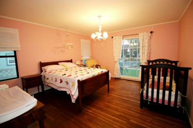 Spacious front bedroom with original hardwood floors. Light and bright!