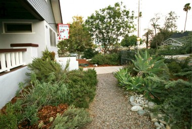 No need to bring a lawnmower to this home. Drought tolerant front yard with pebble walkways and wood chips. Super practical and charming.