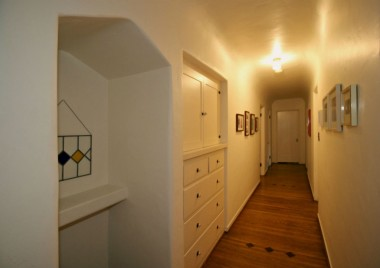 Amazing hallway with telephone alcove and deep linen closet, as well as large walk-in closet at other end.