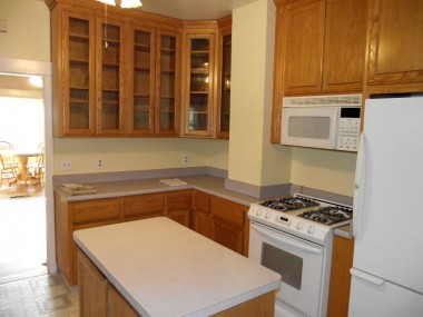 Remodeled kitchen with gas stove, built-in microwave, and preparation island.