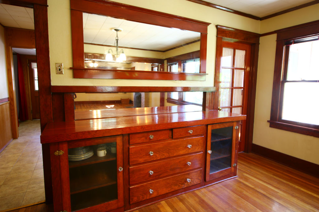 Original built-in hutch in formal dining area. Framed mirror above hutch is a reproduction. Door to right of hutch is a bonus room (could be used as office or 3rd bedroom, or use to extend the kitchen).