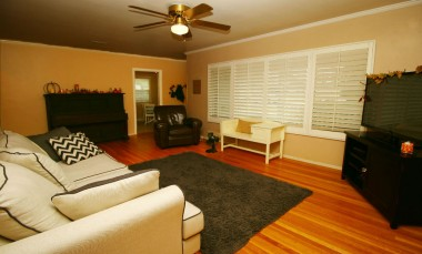 Living room with gorgeous hardwood  floors, window shutters, and ceiling fan.