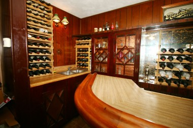 Alternate view of bar with sink and lots of wine racks and cabinetry.