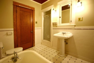 Alternate view of bathroom with separate shower and lights flanking the medicine cabinet above the newer pedestal sink.