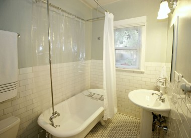 Lovely bathroom with tile floor, pedestal sink, and claw foot tub.