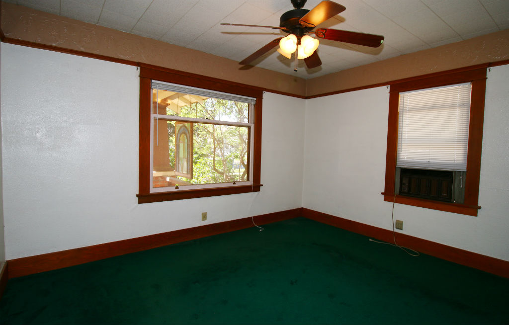Front and back bedrooms are similar in size with hardwood floors (condition unknown) under carpeting. Both bedrooms have good size closets too.