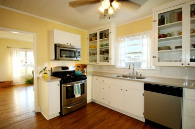 Remodeled kitchen is simply gorgeous, with stone counters, stainless steel appliances, and glass-fronted cabinets.
