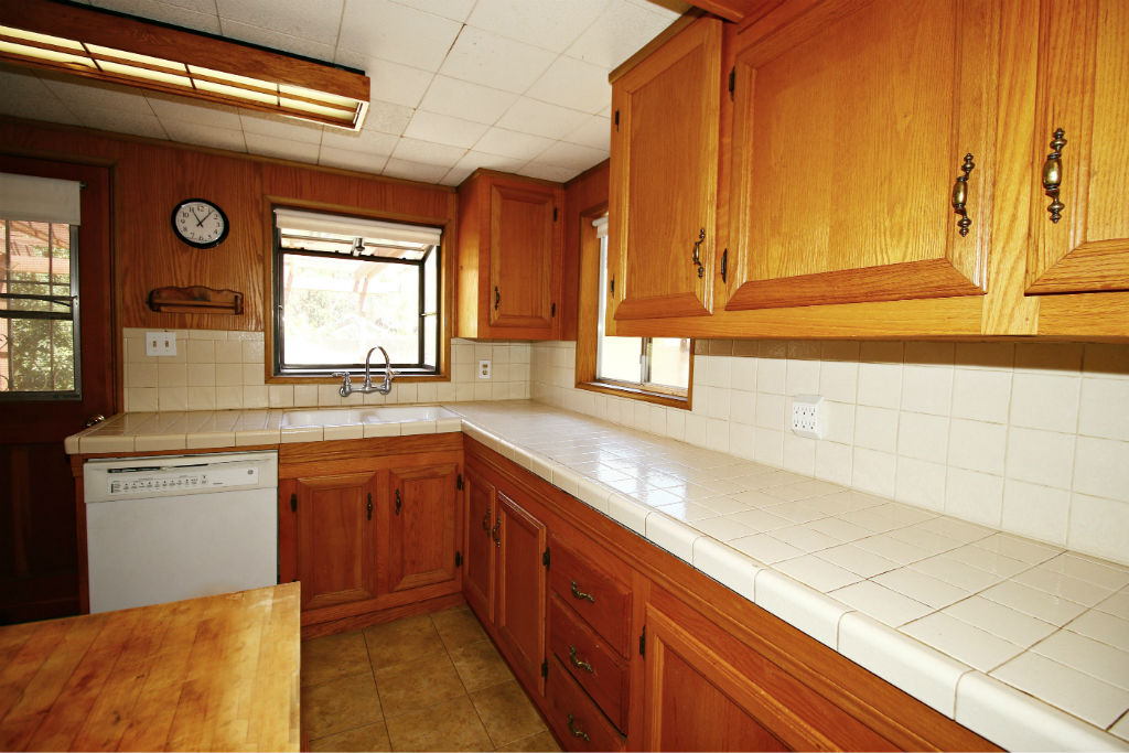 Updated kitchen with LOTS of cabinetry, dishwasher, tiled counter tops, and garden window.