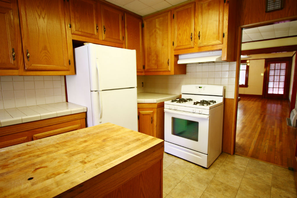 Updated kitchen with tile flooring, tiled counter tops, newer gas stove, LOTS of cabinetry, and a butcher block preparation island.
